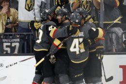 Members of the Vegas Golden Knights celebrate a goal by Vegas Golden Knights left wing Tomas Nosek, of the Czech Republic, during the third period in Game 1 of the NHL hockey Stanley Cup Finals against the Washington Capitals Monday, May 28, 2018, in Las Vegas. (AP Photo/John Locher)