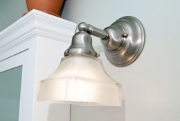 Closeup of a brushed nickel and frosted glass bathroom light fixture in a light blue bathroom.