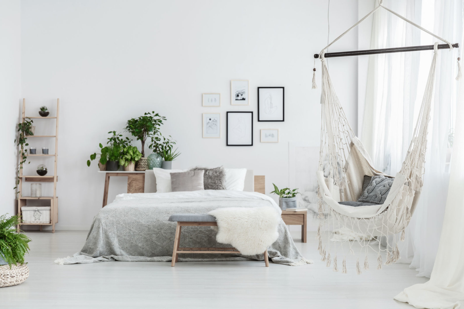Brazilian chair with decorative cushion hanging in white bedroom with posters and green plants