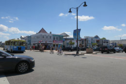 Bethany Beach street with people biking and the trolley is seen