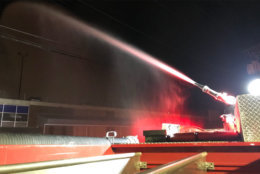 photo shows a fire hose spraying on a warehouse fire in DC