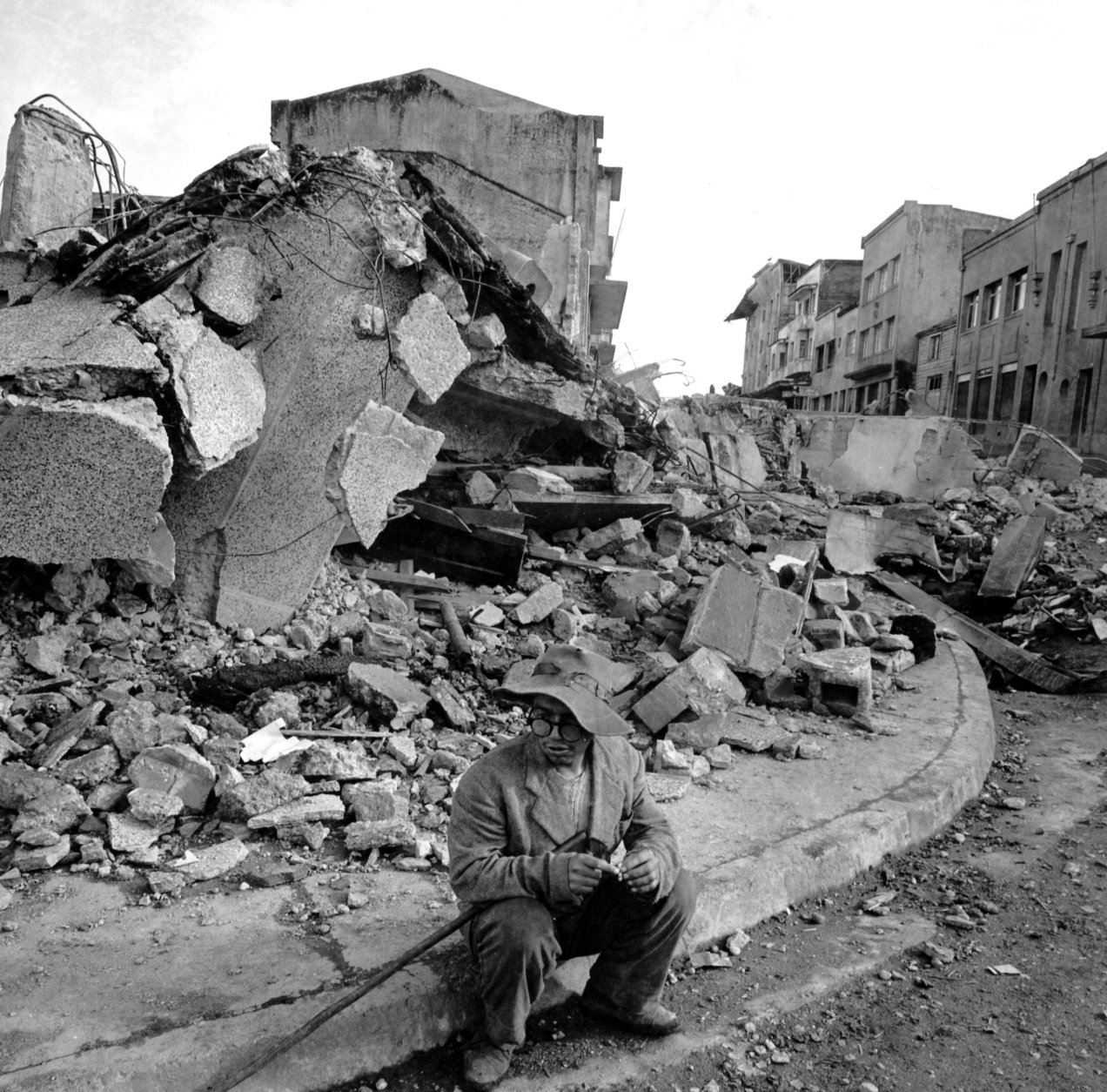 A lone resident of the southern Chile town of Castro sits on a curb in the downtown area after the section was hit by devastating earthquakes.  The rubble in the backround was once  business establishments.  (AP Photo/William J. Smith)