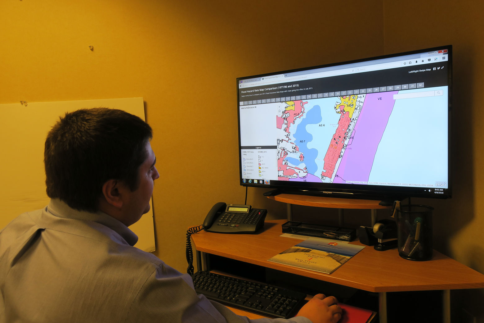 Joe Wilson sits in front of a computer with a flood map up