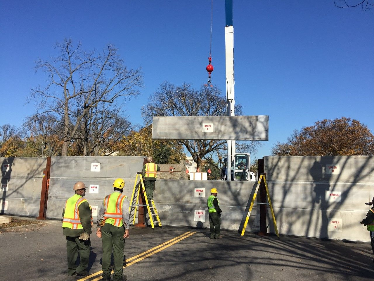 Cranes lower aluminum panels and steel poles into place along 17th Street NW, during erection of the Potomac Park levee. (Courtesy National Park Service)