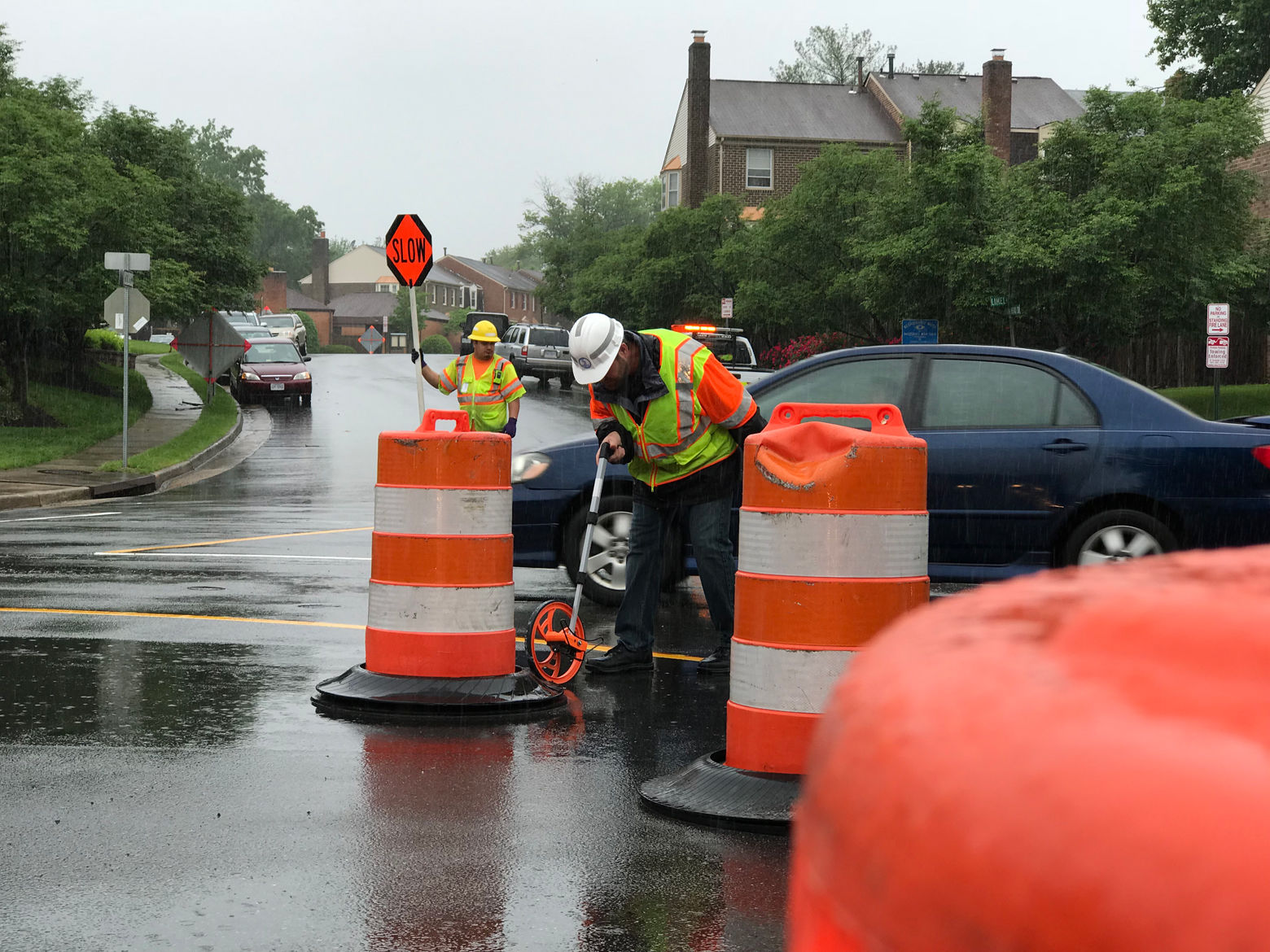A worker sets construction barrels on Ravensworth Road ahead of the installation of a mini roundabout. (Courtesy VDOT)