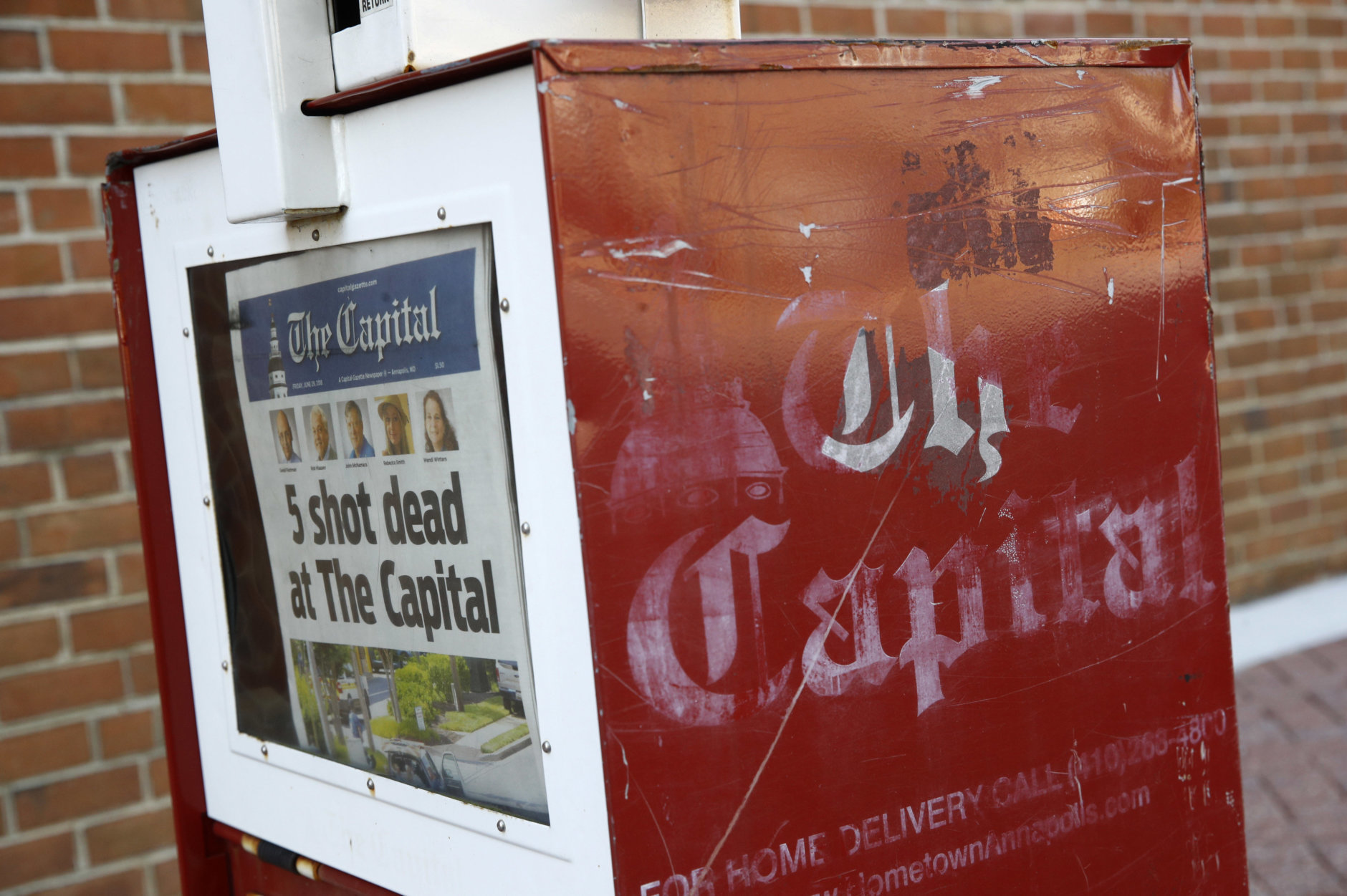 A Capital Gazette newspaper rack displays the day's front page, Friday, June 29, 2018, in Annapolis, Md. A man armed with smoke grenades and a shotgun attacked journalists in the newspaper's building Thursday, killing several people before police quickly stormed the building and arrested him, police and witnesses said. (AP Photo/Patrick Semansky)