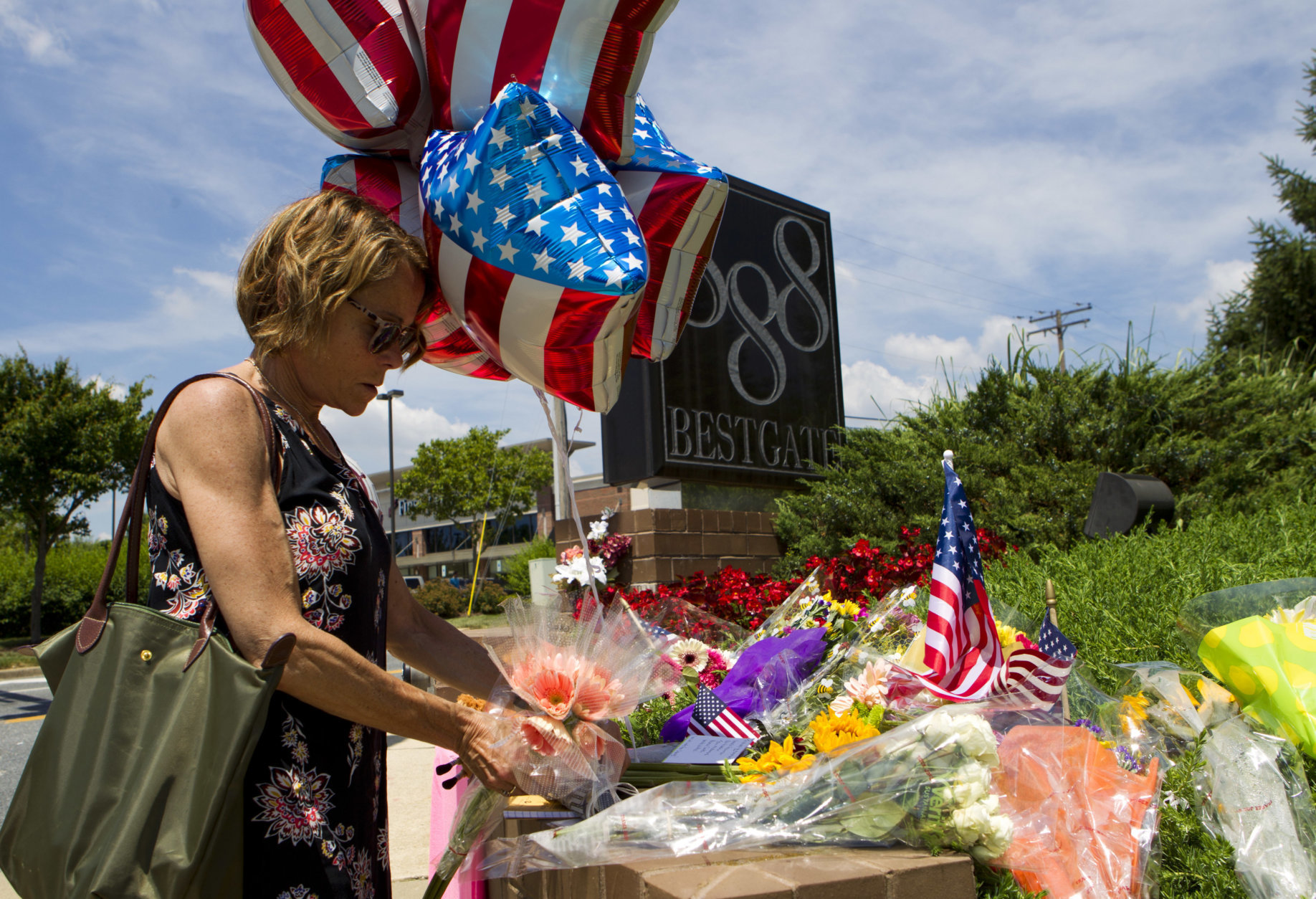 Neighbor Elly M. Tierney places flowers at a makeshift memorial at the scene outside the office building housing The Capital Gazette newspaper in Annapolis, Md., on Friday, June 29, 2018. A man armed with smoke grenades and a shotgun attacked journalists in the building Thursday, killing several people before police quickly stormed the building and arrested him, police and witnesses said. (AP Photo/Jose Luis Magana)