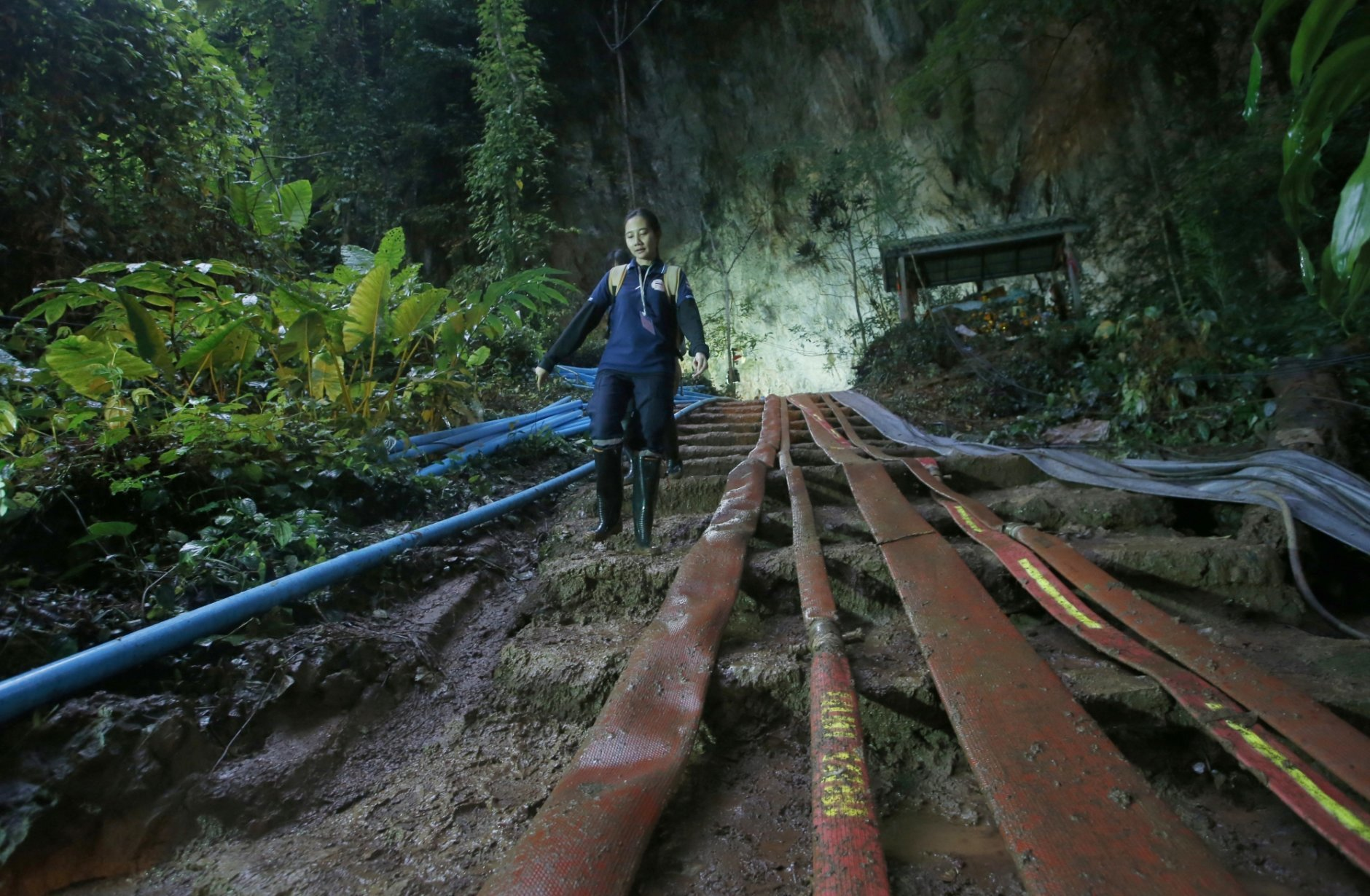 A rescuer makes her way down muddy steps past water pump hoses at the entrance to a cave complex where it's believed that 12 soccer team members and their coach went missing, Friday, June 29, 2018, in Mae Sai, Chiang Rai province, in northern Thailand. (AP Photo/Sakchai Lalit)