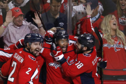 Washington Capitals forward Devante Smith-Pelly, center, celebrates his goal against the Vegas Golden Knights with Matt Niskanen, left, and Chandler Stephenson, during the third period in Game 3 of the NHL hockey Stanley Cup Final, Saturday, June 2, 2018, in Washington. (AP Photo/Pablo Martinez Monsivais)