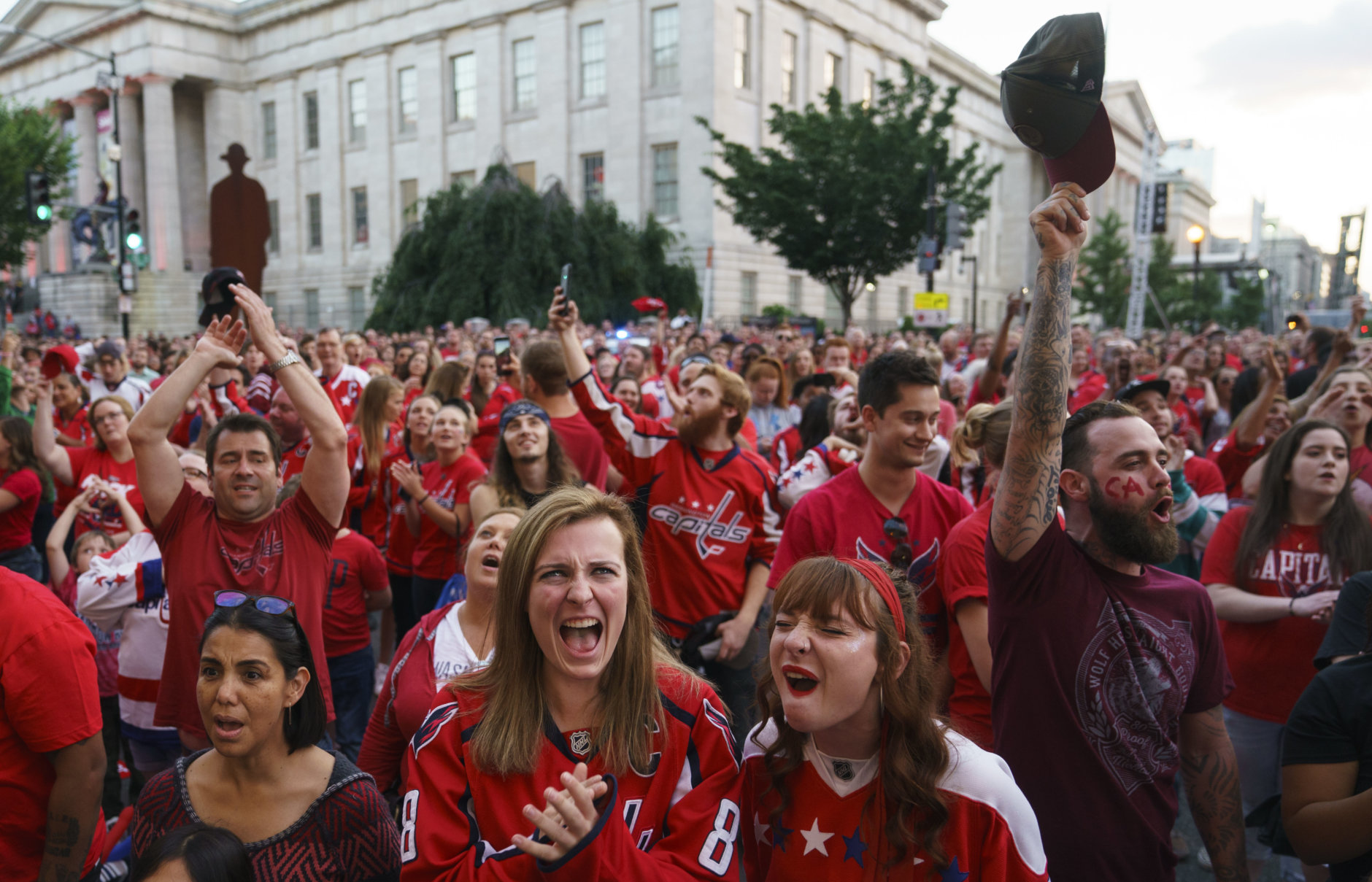 Fans cheer at the conclusion of the National Anthem as they gather in front of Capitol One Arena to watch of Game 4 of the NHL hockey Stanley Cup Final between the Washington Capitals and the Vegas Golden Knights, Monday, June 4, 2018, in Washington. (AP Photo/Carolyn Kaster)