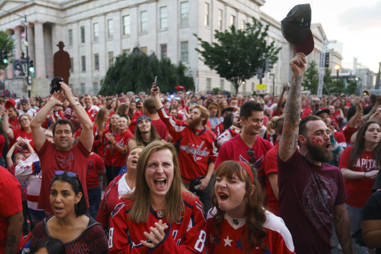 1782fee3f21 Fans cheer at the conclusion of the National Anthem as they gather in front  of Capitol One Arena to watch of Game 4 of the NHL hockey Stanley Cup.