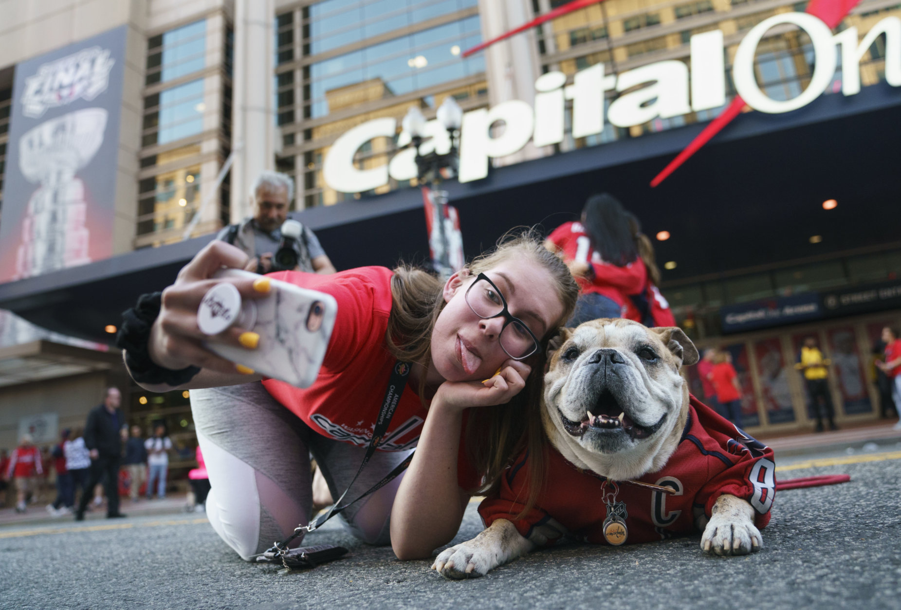 A Washington Capitals fan poses for a photo with Ovie the Bulldog outside Capitol One Arena before Game 4 of the NHL hockey Stanley Cup Final between the Capitals and the Vegas Golden Knights, Monday, June 4, 2018, in Washington. (AP Photo/Carolyn Kaster)