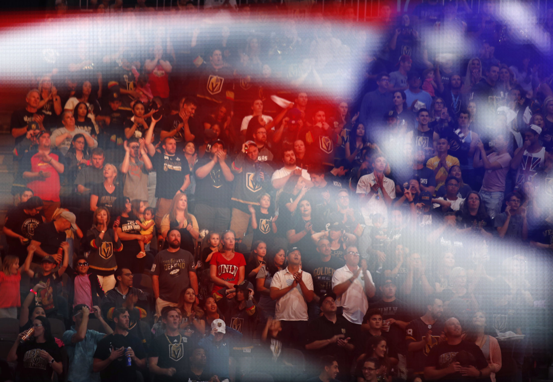 Fans stand for the national anthem during a watch party for Game 4 of the NHL hockey Stanley Cup Final between the Washington Capitals and the Vegas Golden Knights, Monday, June 4, 2018, in Las Vegas. (AP Photo/John Locher)