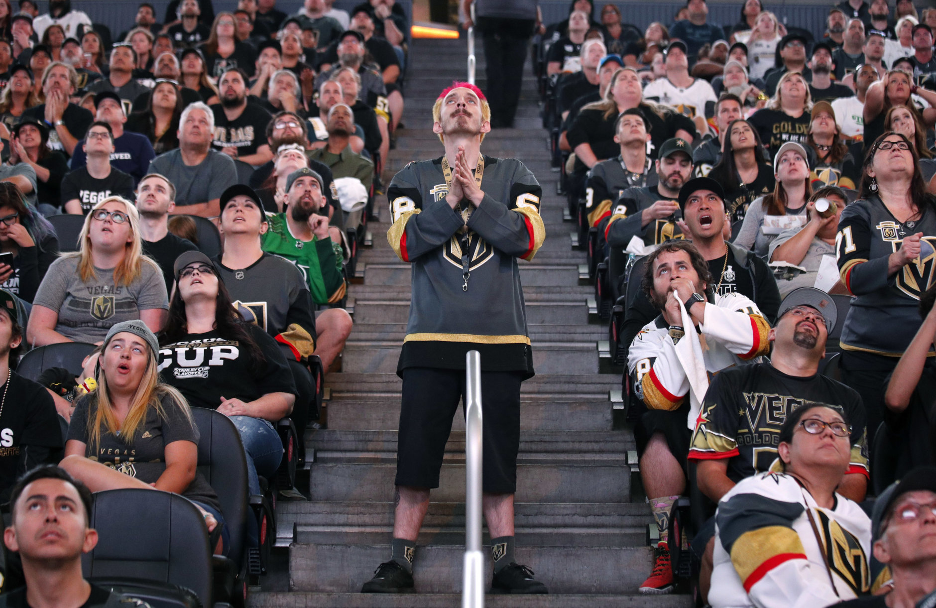 Jay Bryant-Chavez, center, reacts after a play during a watch party for Game 4 of the NHL hockey Stanley Cup Final between the Washington Capitals and the Vegas Golden Knights, Monday, June 4, 2018, in Las Vegas. (AP Photo/John Locher)