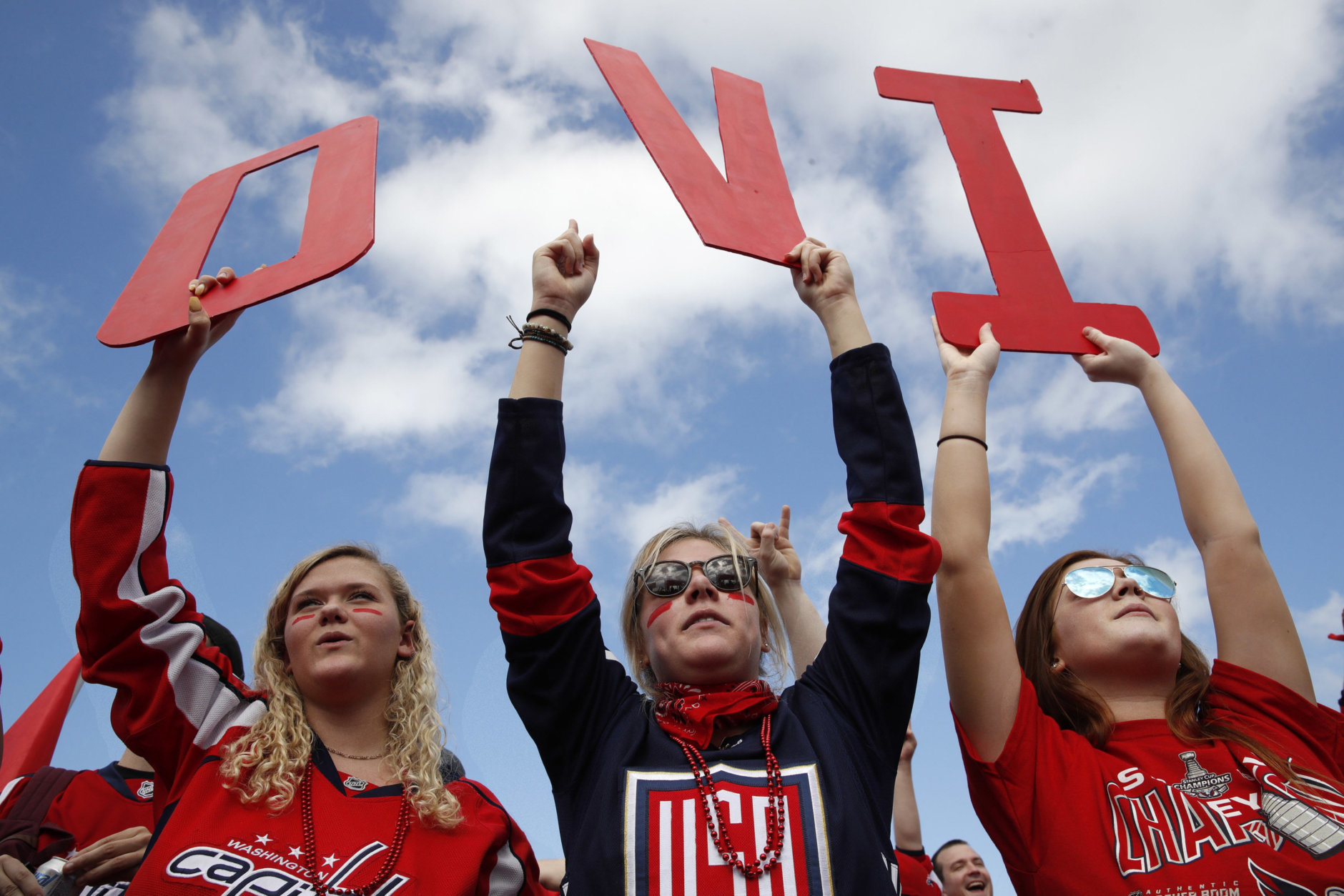 Olivia Spicer, 16, left, Emma Jacobs, 17, and Caroline Schwartz, 18, all of Gainesville, Va., hold up letters spelling the nickname of Washington Capitals' left wing Alex Ovechkin, from Russia, on the National Mall ahead of a victory parade and rally for the Washington Capitals as hockey fans celebrate their winning the Stanley Cup, Tuesday, June 12, 2018, in Washington. (AP Photo/Jacquelyn Martin)