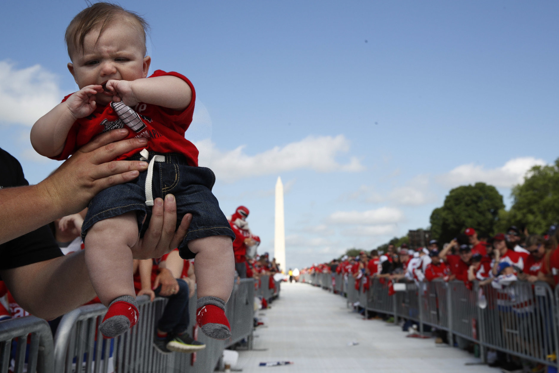 Four-month-old hockey fan C.J. Ford, of Elliott City, Md., is held up by his father as fans line the National Mall ahead of a victory parade and rally for the Washington Capitals in celebration of winning the Stanley Cup, Tuesday, June 12, 2018, in Washington. The baby has already been to eleven games as his parents are season ticket holders. (AP Photo/Jacquelyn Martin)