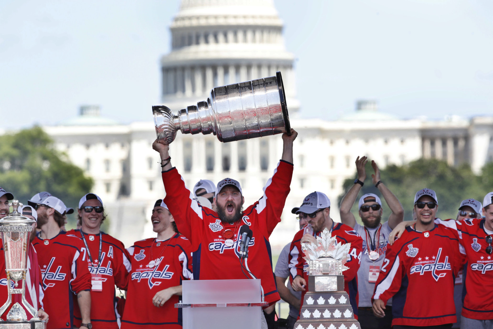 Washington Capitals' Alex Ovechkin, of Russia, holds up the Stanley Cup trophy during the NHL hockey team's Stanley Cup victory celebration, Tuesday, June 12, 2018, at the National Mall in Washington. The U.S. Capitol rises in the background. (AP Photo/Jacquelyn Martin)