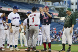 Rep. Steve Scalise, R-Louisiana, center, is announced onto the field at the start of the 57th Congressional Baseball Game at National's Park in Washington, Thursday, June 14, 2018. On June 14, 2017, Scalise and some other Congressional members were victims of a shooting at the baseball field they were practicing on in Alexandria, Va. (AP Photo/Cliff Owen)