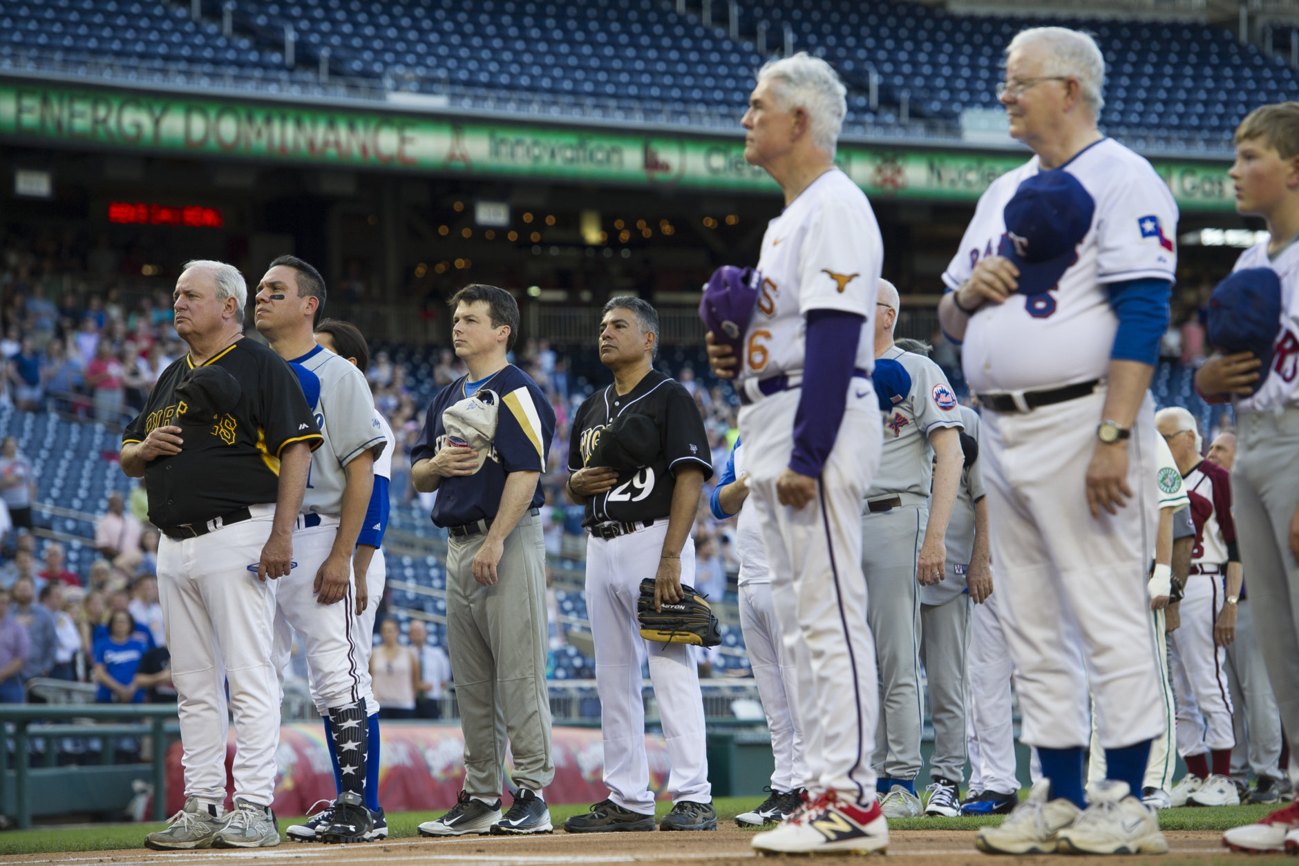 Members of the Democratic and Republican baseball teams stand for the national anthem to start the 57th Congressional Baseball Game at National's Park in Washington, Thursday, June 14, 2018. On June 14, 2017, some Congressional members were victims of a shooting at the baseball field they were practicing on in Alexandria, Va. (AP Photo/Cliff Owen)