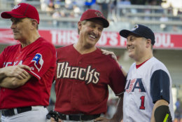 Rep. Jeff Flake, R-Ariz., center, talks with Rep. Steve Scalise, R- La., at the start of the 57th Congressional Baseball Game at National's Park in Washington, Thursday, June 14, 2018. Scalise, the House majority whip who was shot at a Republican baseball practice a year ago, fielded a ground ball and threw out the first batter of the annual congressional baseball game Thursday. (AP Photo/Cliff Owen)