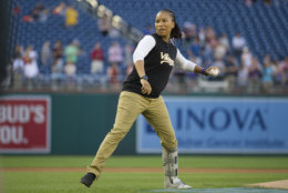 Capitol Hill Police Special Agent Crystal Griner throws out the first pitch to start the 57th Congressional Baseball Game at National's Park in Washington, Thursday, June 14, 2018. On June 14, 2017, Congressional members were victims of a shooting at the baseball field they were practicing on in Alexandria, Va. (AP Photo/Cliff Owen)