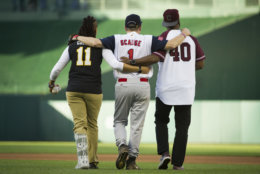 Capitol Police Special Agents Crystal Griner, left, and David Bailey, right, assist U.S. Rep. Steve Scalise to his position at second base at the start of the 57th Congressional Baseball Game at National's Park in Washington, Thursday, June 14, 2018. On June 14, 2017, Scalise was wounded in the leg when he and other Congressional members were the victims of a shooting at the baseball field they were practicing on in Alexandria, Va. (AP Photo/Cliff Owen)
