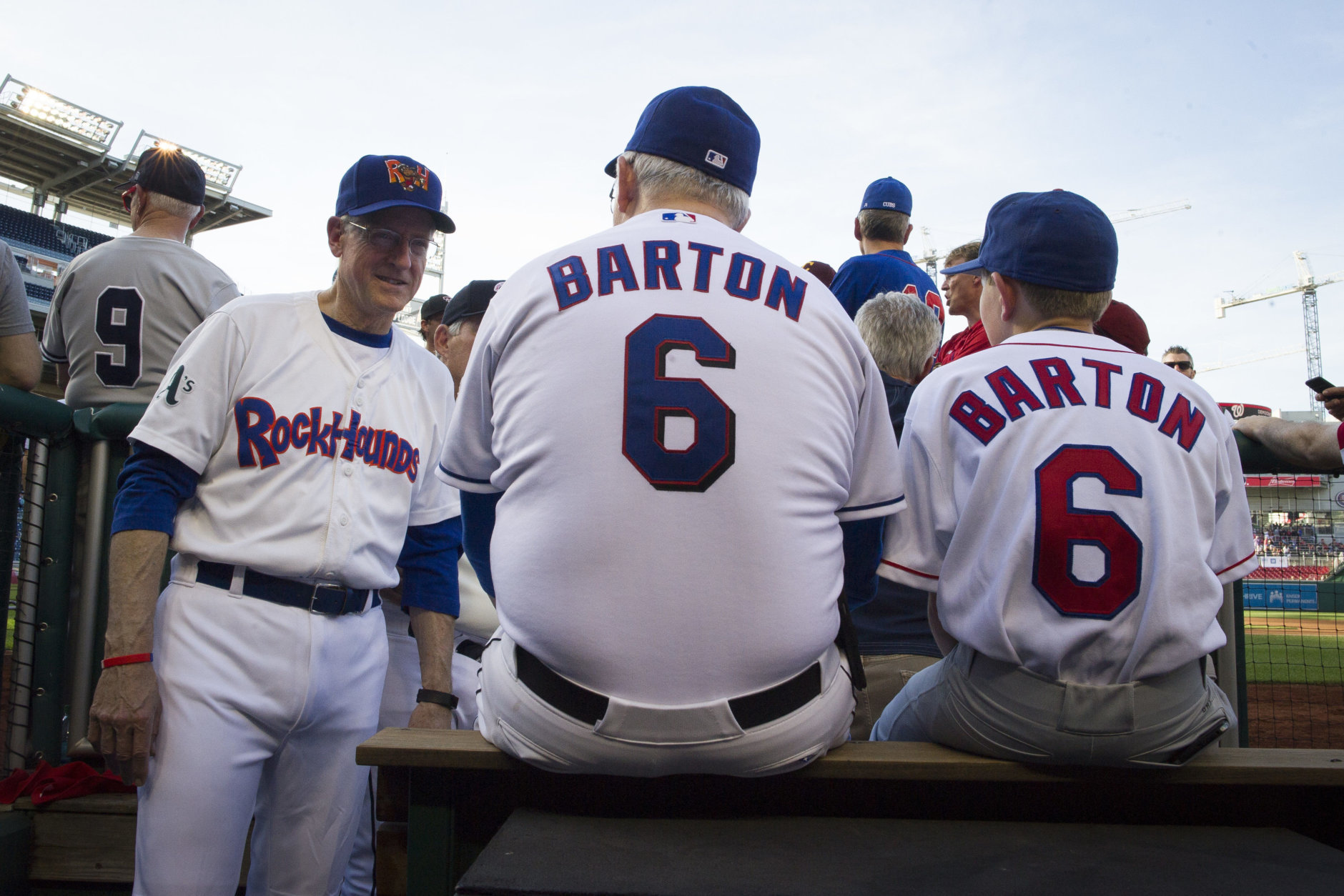 Rep. Mike Conaway, R-Texas, left talks with Rep. Joe Barton, R-Texas, and his son Jack, 12, while they sit in the Republican team dugout during the 57th Congressional Baseball Game at National's Park in Washington, Thursday, June 14, 2018. On June 14, 2017, Congressional members were victims of a shooting at the baseball field they were practicing on in Alexandria, Va. (AP Photo/Cliff Owen)