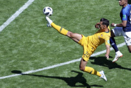 Australia's Trent Sainsbury, center, kicks the ball in front of France's Kylian Mbappe during the group C match between France and Australia at the 2018 soccer World Cup in the Kazan Arena in Kazan, Russia, Saturday, June 16, 2018. (AP Photo/Hassan Ammar)