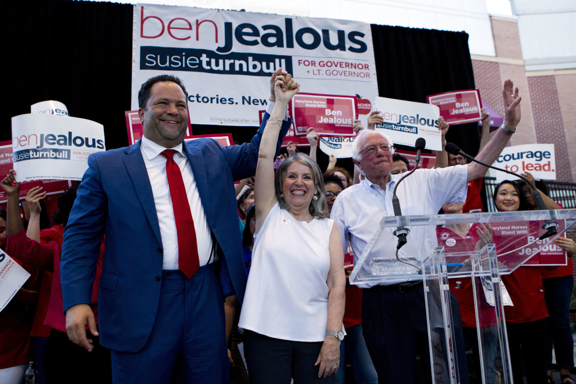 Democrat Ben Jealous, left, raises the hand of his running mate Susie Turnbull, while Sen. Bernie Sanders, I-Vt., waves during a gubernatorial campaign rally in Maryland's Democratic primary in downtown Silver Spring, Md., Monday, June 18, 2018. Sanders may not be endorsing his own son's congressional bid, but he rallied on a hot Monday night in Maryland to fire up voters for Jealous' campaign for governor. (AP Photo/Jose Luis Magana)