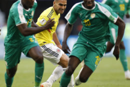 Colombia's Radamel Falcao, center, watches the ball behind Senegal's Lamine Gassama, left, and Senegal's Sadio Mane during the group H match between Senegal and Colombia, at the 2018 soccer World Cup in the Samara Arena in Samara, Russia, Thursday, June 28, 2018. (AP Photo/Efrem Lukatsky)