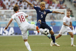 Japan's Yuto Nagatomo, center, and Poland's Bartosz Bereszynski vie for the ball during the group H match between Japan and Poland at the 2018 soccer World Cup at the Volgograd Arena in Volgograd, Russia, Thursday, June 28, 2018. (AP Photo/Eugene Hoshiko)