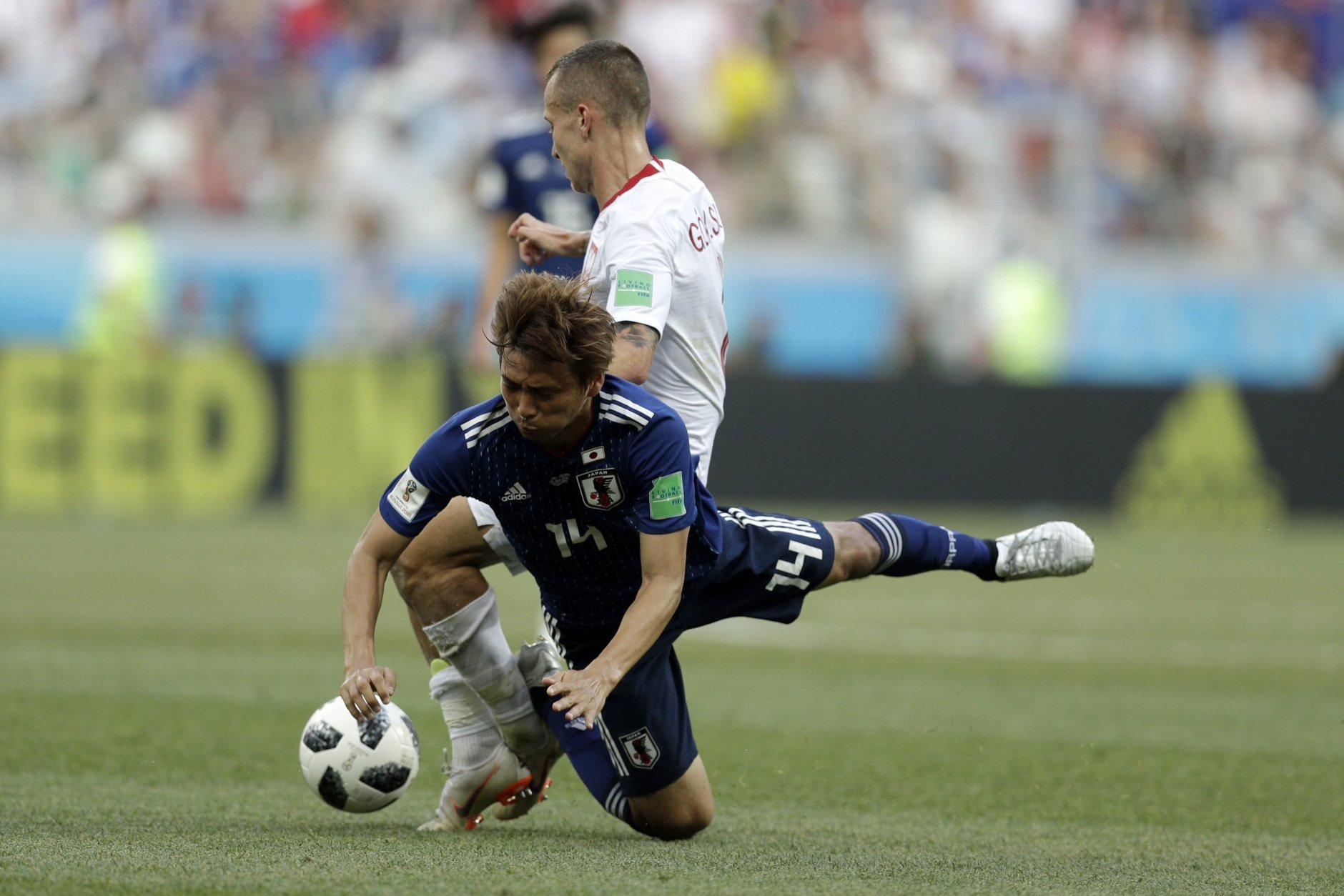 Poland's Jacek Goralski, background, stops Japan's Takashi Inui during the group H match between Japan and Poland at the 2018 soccer World Cup at the Volgograd Arena in Volgograd, Russia, Thursday, June 28, 2018. (AP Photo/Andrew Medichini)