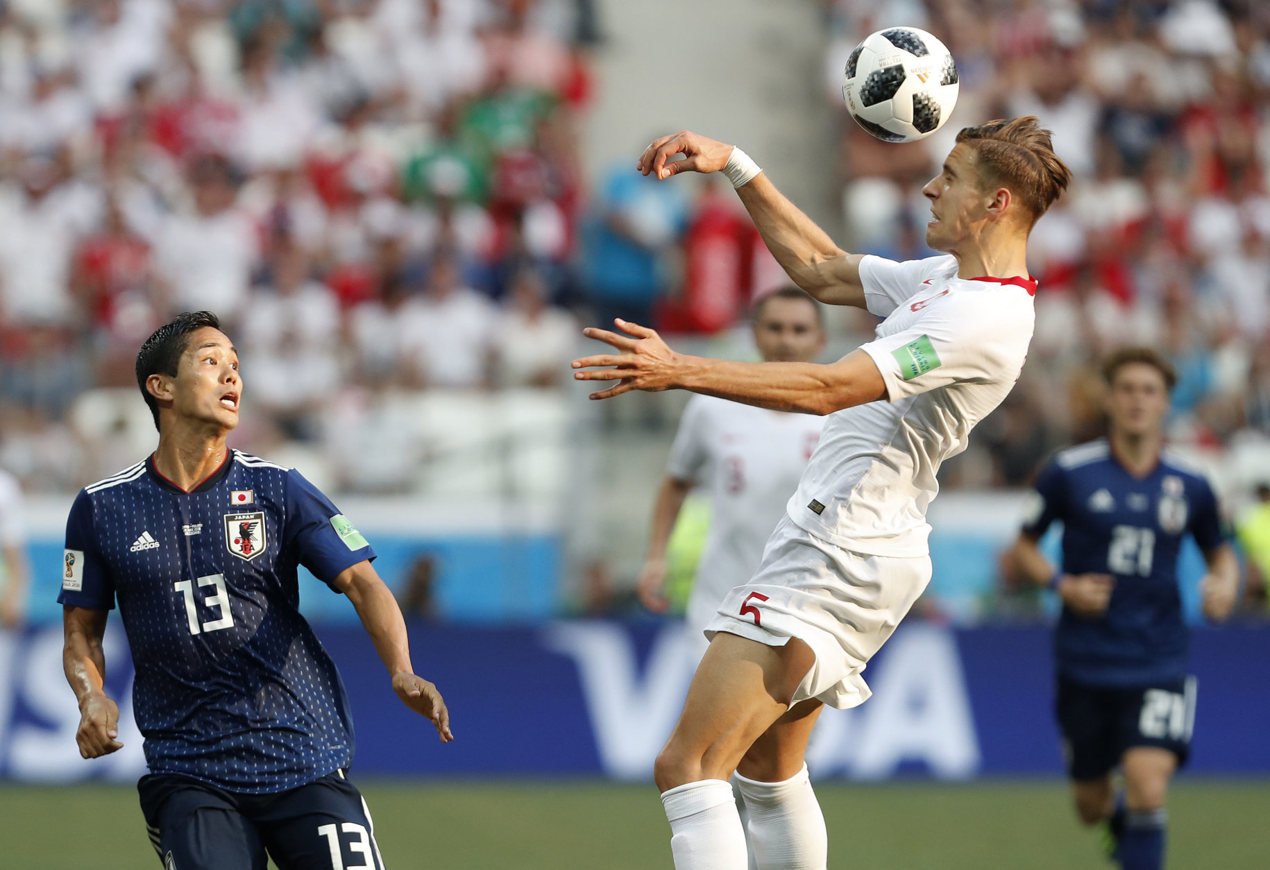 Poland's Jan Bednarek clears the ball from Japan's Yoshinori Muto during the group H match between Japan and Poland at the 2018 soccer World Cup at the Volgograd Arena in Volgograd, Russia, Thursday, June 28, 2018. (AP Photo/Darko Vojinovic)