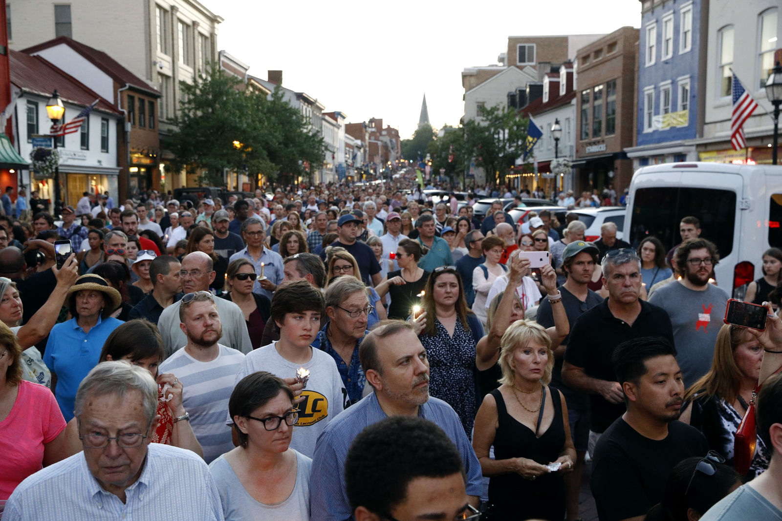 Mourners walk during a vigil in response to a shooting at The Capital Gazette newspaper office, Friday, June 29, 2018, in Annapolis, Md. The suspect, Jarrod W. Ramos, is charged with five counts of first-degree murder in one of the deadliest attacks on journalists in U.S. history. (AP Photo/Patrick Semansky)