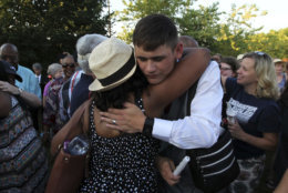 People hug during a candlelight vigil across the street from where five journalists were slain in their newsroom in Annapolis, Md., Friday, June 29, 2018. Prosecutors say Jarrod W. Ramos opened fire Thursday in the Capital Gazette newsroom. (AP Photo/Jose Luis Magana)