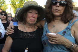 People gather for a candlelight vigil across the street from where five journalists were slain in their newsroom in Annapolis, Md., Friday, June 29, 2018. Prosecutors say Jarrod W. Ramos opened fire Thursday in the Capital Gazette newsroom. (AP Photo/Jose Luis Magana)