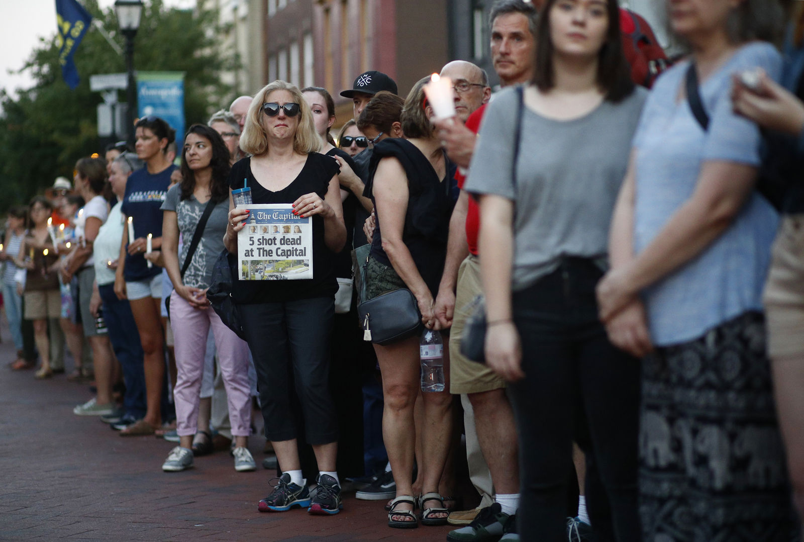 People stand in silence during a vigil in response to a shooting in the Capital Gazette newsroom Friday, June 29, 2018, in Annapolis, Md. Prosecutors say Jarrod W. Ramos opened fire Thursday in the newsroom. (AP Photo/Patrick Semansky)