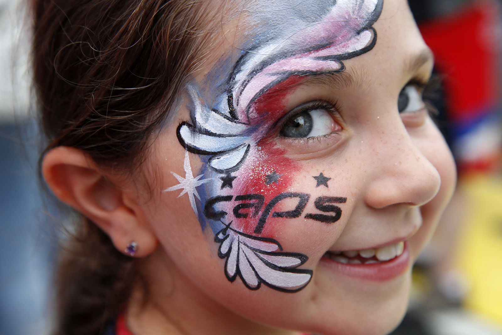 Sarah Charapp, 8, of Potomac, Md., shows off her painted face in support of the Washington Capitals, as fans gather to watch Game 3 of the NHL hockey Stanley Cup Final between the Capitals and the Vegas Golden Knights, Saturday, June 2, 2018, in Washington. (AP Photo/Jacquelyn Martin)