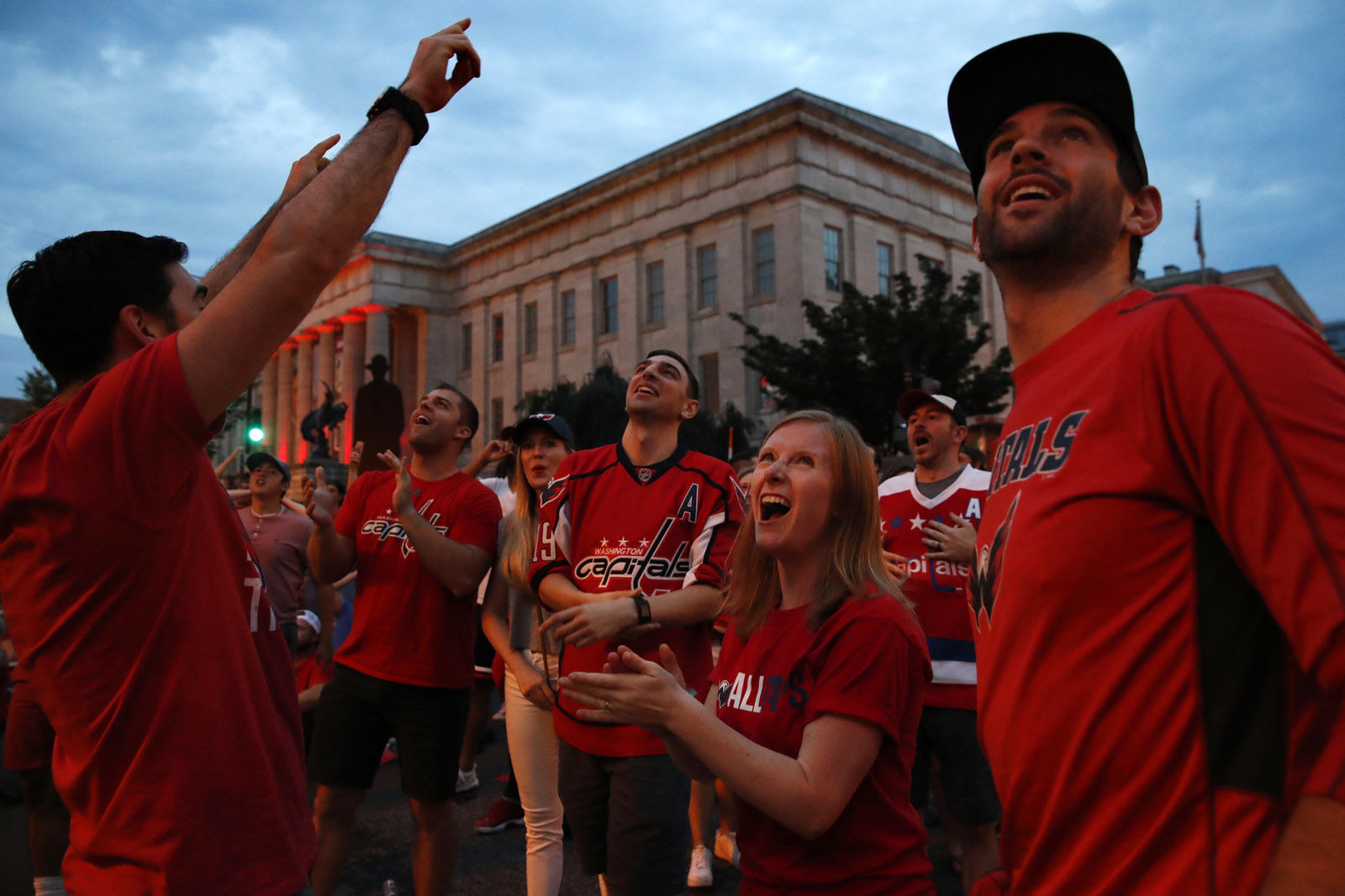 Jack Hanlon, left, of Alexandria, Va.; Allison Baden, of Alexandria; and Adam Abramson, right, of Washington, react to a goal that they thought was scored by the Washington Capitals, as they watch Game 3 of the NHL hockey Stanley Cup Final between the Washington Capitals and the Vegas Golden Knights on a large screen outside the arena Saturday, June 2, 2018, in Washington. (AP Photo/Jacquelyn Martin)