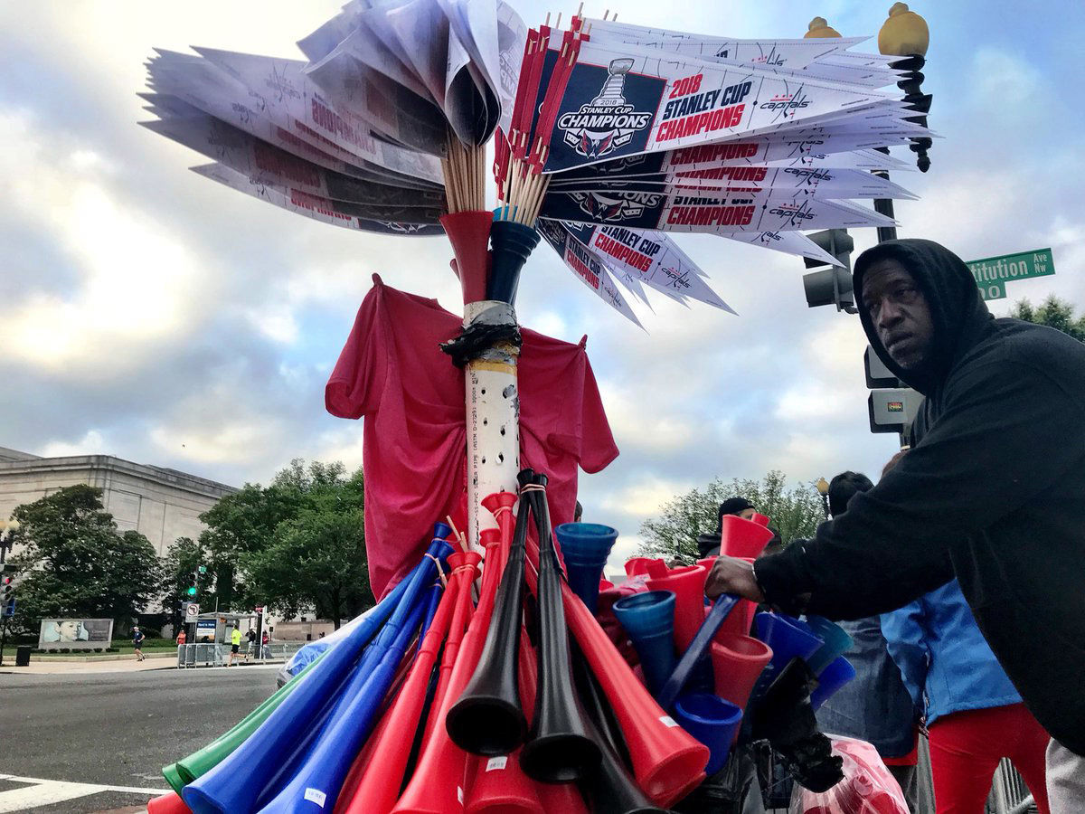 A vendor sells Caps' pennants along the parade route. (WTOP/Neal Augenstein)