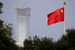 """FILE - In this Thursday, June 14, 2018, file photo, a Chinese national flag at Tiananmen Square flutters against the capital city tallest skyscraper China Zun Tower under construction at the Central Business District in Beijing. China has threatened """"comprehensive measures"""" in response to U.S. President Donald Trump's new tariff hike, raising the possibility Beijing might target operations of American companies. (AP Photo/Andy Wong, File)"""