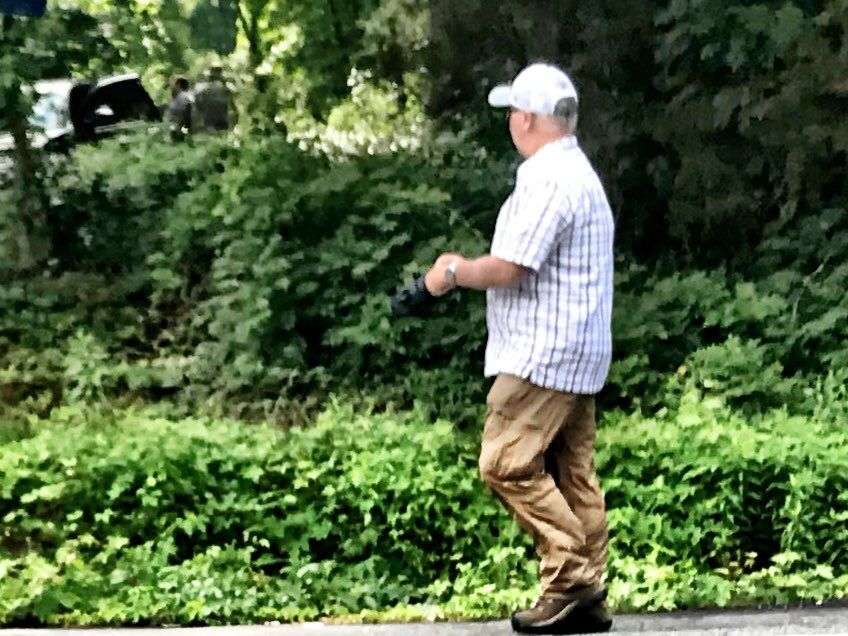 An FBI crime scene investigator puts on gloves approaching scene of Bijan Ghaisar shooting. (WTOP/Neal Augenstein)