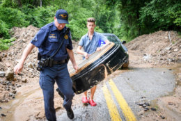 A Howard County officer helps Mark Haver carry the Ellicott City clock, which was swept away during Sunday's flood. (Courtesy Howard County Government)