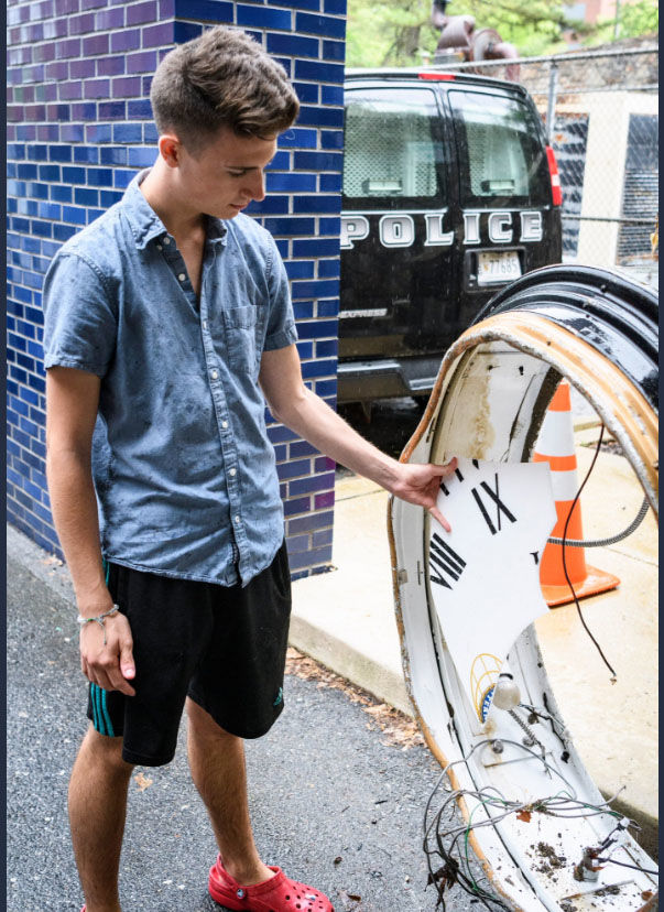 Mark Haver holds up a piece of the Ellicott City clock that was swept away during the flood and recovered Saturday, June 2, 2018. (Courtesy Howard County Government)