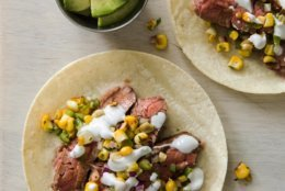 """This undated photo provided by America's Test Kitchen in May 2018 shows flank steak tacos with charred corn salsa in Brookline, Mass. This recipe appears in the cookbook """"Cook It In Cast Iron."""" (Joe Keller/America's Test Kitchen via AP)"""