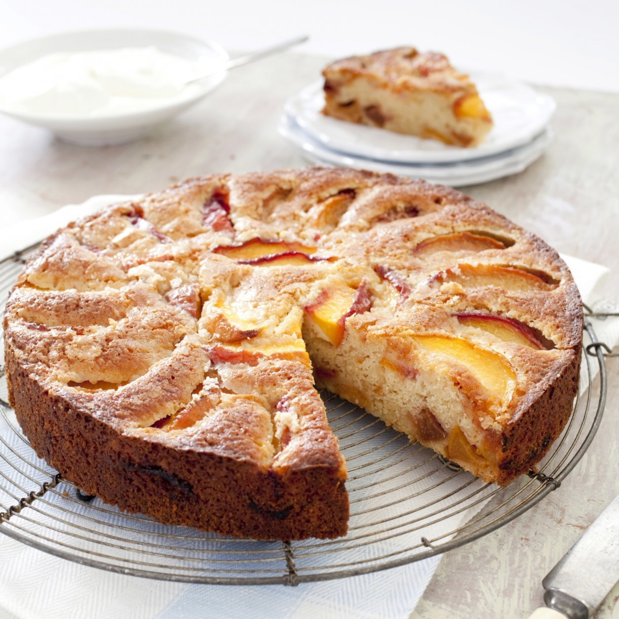 """This undated photo provided by America's Test Kitchen in May 2018 shows summer peach cake in Brookline, Mass. This recipe appears in the cookbook """"The Perfect Cake."""" (Carl Tremblay/America's Test Kitchen via AP)"""
