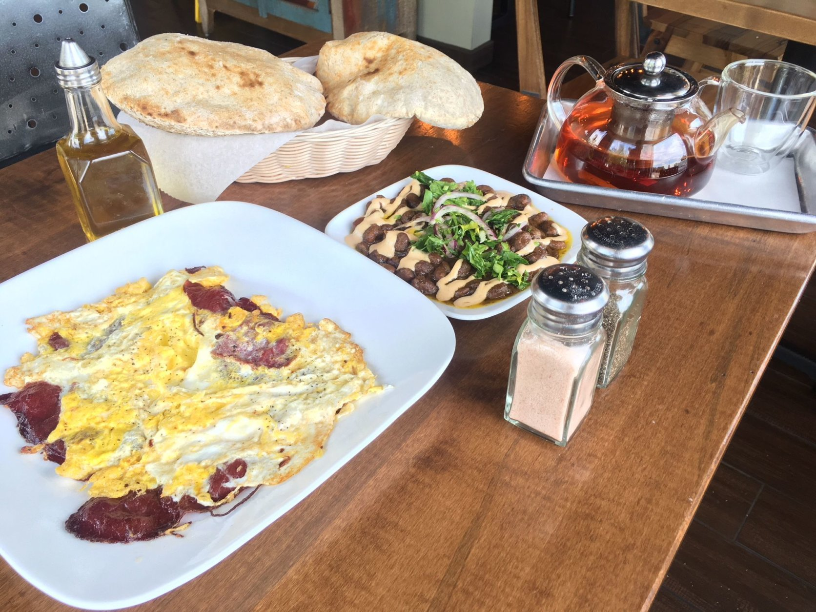 The breakfast spread at Fava Pot, including ful medames, basturma and eggs, and fresh-baked aish baladi. (WTOP/Noah Frank)