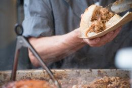 Man in grey T shirt serving pulled pork street food holding sandwich with rind and serving tongs in the foreground