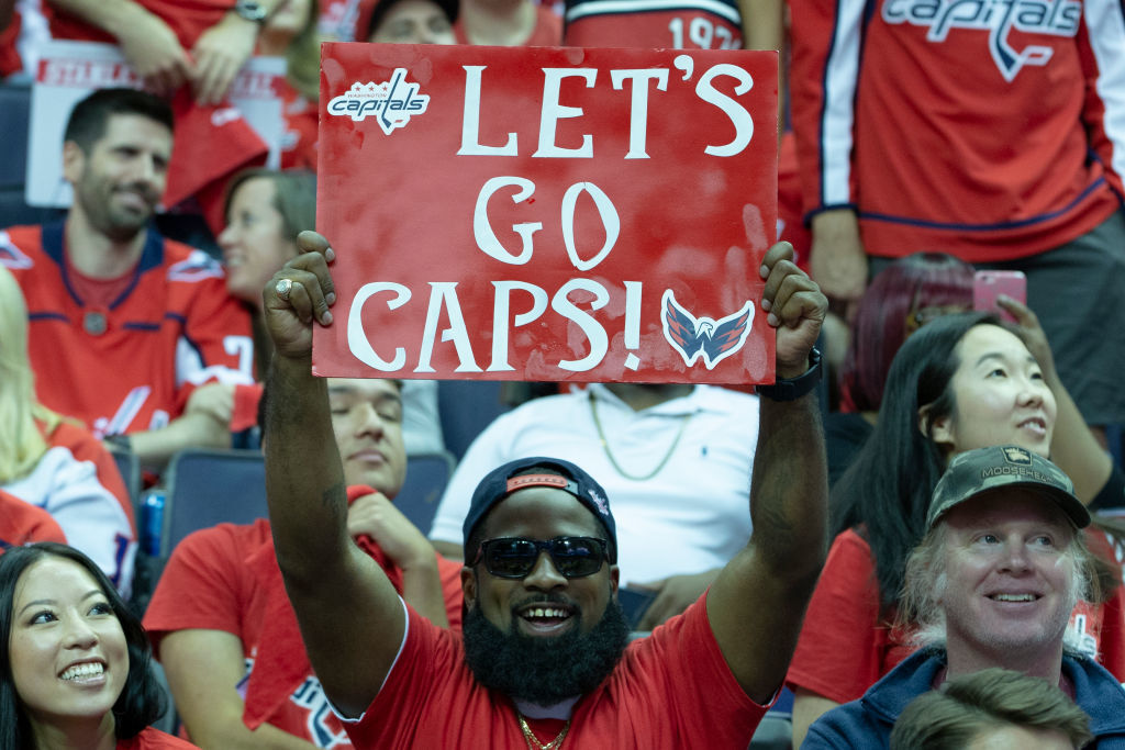 """WASHINGTON, DC - JUNE 07: A Washington Capitals fan holds a """"Lets Go Caps"""" sign during the fan watch party at Capitol One Area on June 7, 2018 in Washington, DC. The Washington Capitals head into Game 5 tonight against the Las Vegas Golden Knights with a  3-1 series lead. (Photo by Alex Edelman/Getty Images)"""