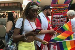 Holding rainbow flags, parade-attendees march on and celebrate Pride Month at D.C.'s Pride Parade. (WTOP/Dick Uliano)
